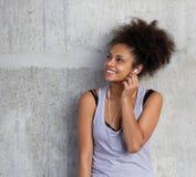 Muchacha hermosa de la raza mixta que sonríe con los auriculares Foto de archivo libre de regalías