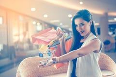 Muchacha hermosa de la sonrisa que sostiene el panier colorido Imagenes de archivo
