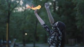 Muchacha hermosa de la tolerancia que realiza una demostración con la llama que se coloca delante de la exhalación experta del ar metrajes