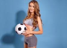 Muchacha hermosa de los deportes que presenta con una bola como futbolista en un fondo azul fotografía de archivo