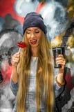 Muchacha hermosa de moda en ropa elegante con caramelo y taza del fondo de la pintada un grandes en sus manos Imagen de archivo libre de regalías