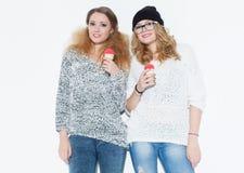 Muchacha hermosa de moda que come el helado y diversión que presenta cerca de una pared blanca indoor estudio Imagen de archivo