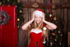 Muchacha hermosa de Papá Noel que se divierte y que sonríe cerca Fotos de archivo libres de regalías