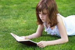 Muchacha hermosa de Park.Young que lee un libro al aire libre Imagen de archivo