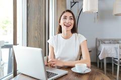 Muchacha hermosa de risa con el ordenador portátil en restaurante Fotografía de archivo libre de regalías