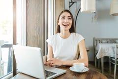 Muchacha hermosa de risa con el ordenador portátil en restaurante Imagen de archivo