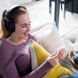Muchacha hermosa de risa con los auriculares que escucha la música en smartphone Fotografía de archivo libre de regalías