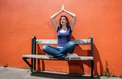 Muchacha hermosa de rogación que disfruta de la relajación en banco en la posición de la yoga imagen de archivo libre de regalías