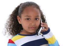 Muchacha hermosa de seis años que habla en el teléfono celular sobre blanco Foto de archivo libre de regalías