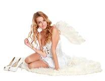 Muchacha hermosa del ángel que se sienta en una alfombra blanca imagen de archivo