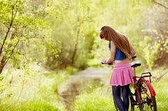 Muchacha hermosa del adolescente cerca de la bicicleta en bosque Fotos de archivo libres de regalías