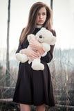Muchacha hermosa del adolescente con el juguete del oso de peluche en manos en fondo del bosque quemado Imágenes de archivo libres de regalías