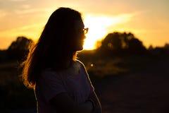 Muchacha hermosa del adolescente con los vidrios en puesta del sol Imagen de archivo