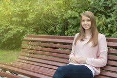 Muchacha hermosa del adolescente en el banco Imágenes de archivo libres de regalías