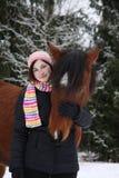 Muchacha hermosa del adolescente que abraza el caballo marrón en invierno Imagen de archivo libre de regalías