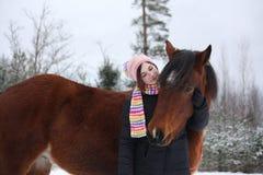 Muchacha hermosa del adolescente que abraza el caballo marrón en invierno Imagenes de archivo