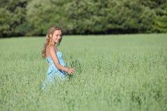 Muchacha hermosa del adolescente que camina en un prado verde de la avena Imagen de archivo