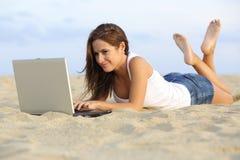 Muchacha hermosa del adolescente que hojea su ordenador portátil que miente en la arena de la playa Imagen de archivo libre de regalías
