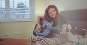 Muchacha hermosa del adolescente que juega en la guitarra en su dormitorio que se siente bien y que disfruta del tiempo relajante almacen de metraje de vídeo