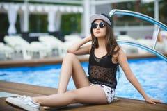 Muchacha hermosa del adolescente que se sienta cerca de la piscina al aire libre Imagenes de archivo