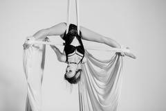 Muchacha hermosa del aerialist que hace trucos acrobáticos Fotografía de archivo libre de regalías