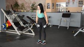 Muchacha hermosa del ajuste que hace ejercicios con el dumbbellsn almacen de metraje de vídeo