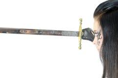 Muchacha hermosa del asesino que mira en la lámina de la espada fotos de archivo libres de regalías