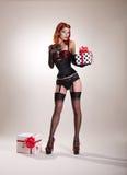 Muchacha hermosa del estilo del perno-para arriba del pelirrojo que sostiene la caja de regalo Fotos de archivo libres de regalías