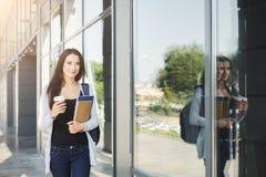 Muchacha hermosa del estudiante con los libros de texto y el café Imagenes de archivo