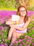 Muchacha hermosa del estudiante en campo de flor Foto de archivo