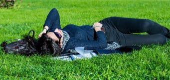 Muchacha hermosa del estudiante que miente en hierba verde y que se relaja Fotos de archivo libres de regalías
