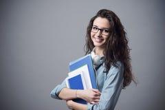 Muchacha hermosa del estudiante que presenta con los cuadernos Fotos de archivo