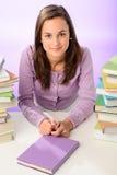 Muchacha hermosa del estudiante que se sienta entre los libros de las pilas Fotos de archivo