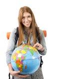 Muchacha hermosa del estudiante que sostiene el globo del mundo en su mano que elige el destino de los días de fiesta en concepto Foto de archivo libre de regalías