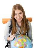 Muchacha hermosa del estudiante que sostiene el globo del mundo en su mano que elige el destino de los días de fiesta en concepto Imagen de archivo