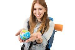Muchacha hermosa del estudiante que sostiene poco globo del mundo en su mano que elige el destino de los días de fiesta en concep Fotos de archivo libres de regalías