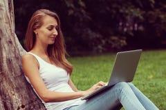 Muchacha hermosa del estudiante que trabaja en su ordenador portátil al aire libre en el día soleado Imagen de archivo libre de regalías