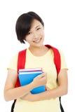 Muchacha hermosa del estudiante universitario que se coloca sobre el fondo blanco Imagen de archivo libre de regalías
