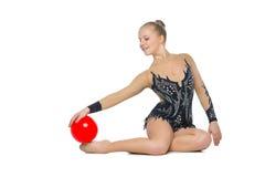 Muchacha hermosa del gimnasta con la bola roja Foto de archivo libre de regalías