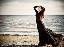 Muchacha hermosa del goth que se coloca en la playa del mar Imagenes de archivo