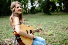 Muchacha hermosa del hippie que toca la guitarra Fotos de archivo libres de regalías