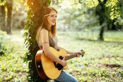Muchacha hermosa del hippie que toca la guitarra Imagen de archivo