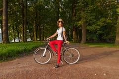 Muchacha hermosa del inconformista en una bicicleta en el parque imagen de archivo