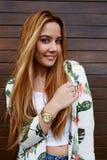muchacha hermosa del inconformista que lleva la ropa de moda que se coloca en fondo de madera de la pared Imagenes de archivo