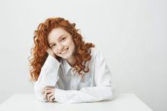 Muchacha hermosa del jengibre con el pelo rizado que sonríe mirando la cámara que se sienta en la tabla sobre el fondo blanco Imagen de archivo libre de regalías