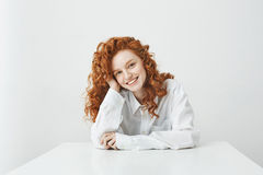 Muchacha hermosa del jengibre con el pelo rizado que sonríe mirando la cámara que se sienta en la tabla sobre el fondo blanco Fotografía de archivo