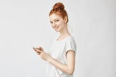 Muchacha hermosa del jengibre que sonríe sosteniendo el teléfono que mira la cámara Foto de archivo