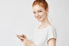 Muchacha hermosa del jengibre que sonríe sosteniendo el teléfono twitting o que usa medios sociales sobre la pared blanca Imágenes de archivo libres de regalías