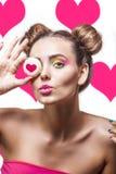 Muchacha hermosa del modelo de moda con las galletas con los corazones en vagos rosados Foto de archivo