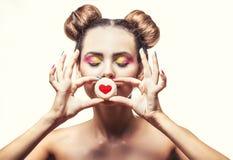 Muchacha hermosa del modelo de moda con las galletas dulces con los corazones en a Foto de archivo libre de regalías